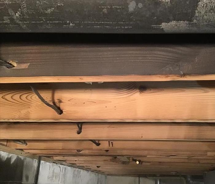 slightly charred and blackened floor joists amongst floor joists that are like new